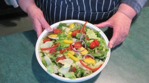 White bowl of colourful shredded leaves, sliced onions and peppers with golden mango pieces.