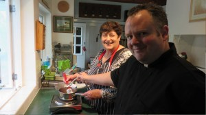 Penny and Mike hovering over a small stainless steel pan of strawberries.