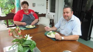 John and Penny sitting at the table in the conservatory ready to taste their  plates of fish.
