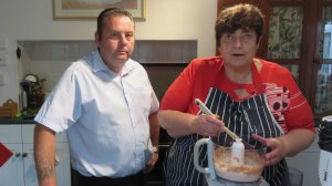 Two cooks with a food processor of pale pink mix.