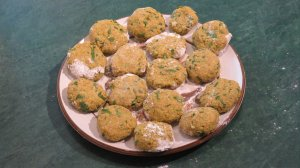About 15 yellow falafels  each flecked with the green parsley set out on the plate so that they don't stick together.