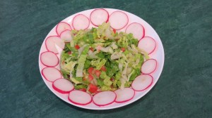A Finely shredded lettuce with thinly sliced cucumber and tomato plus slices of radish ready to add to the wraps.