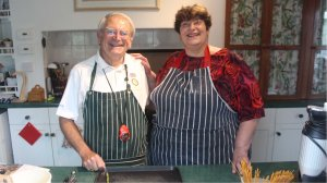 Roger and Penny dressed in their stripey aprons in the kitchen ready to start the dish.